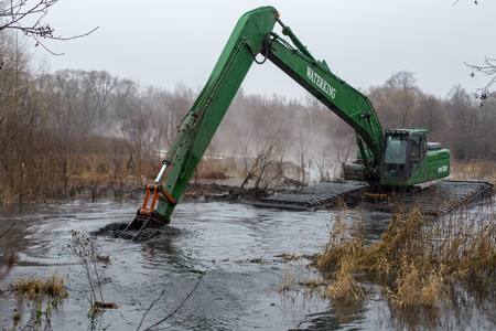 Balashikha, Moscow area, Russia - December 14, 2017: The floating excavator removes silt from the Pekhorka river bed Редакционное