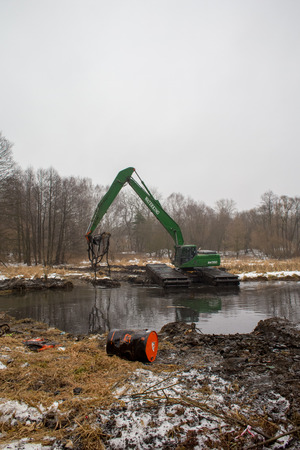 Balashikha, Moscow area, Russia - December 14, 2017: The floating excavator removes silt from the Pekhorka river bed Editorial