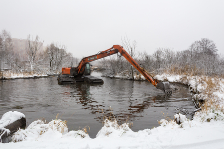 Balashikha, Moscow area, Russia - December 19, 2018: The floating excavator cleans the Malashka river bed from silt and garbage Editorial