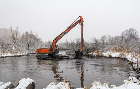 Balashikha, Moscow area, Russia - December 19, 2018: The floating excavator cleans the Malashka river bed from silt and garbage Редакционное