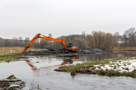 Balashikha, Moscow region, Russia - December, 2017: Excavator removes silt from the bottom of the river Pekhorka