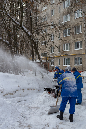 Balashikha, Moscow region, Russia - March 5, 2018: Janitors clean the snow in the yard after a heavy snowfall