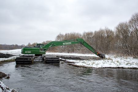 Balashikha, Moscow area, Russia - January 05, 2017: The excavator cleans the Pekhorka river bed from silt and threaten.