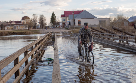 Kholuy, Ivanovo region, Russia - April 27, 2018: Crossing the water by bicycle through the bridge in the village of Kholui, Yuzhsky district, Ivanovo region, during the spring flood of the Teza River