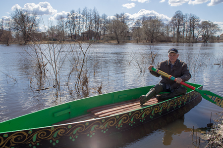 Kholuy, Ivanovo Region, Russia - April 27, 2018: Revival of the old tradition, the artistic painting of boats and their descent into the water during the spring flood of the Teza River Редакционное