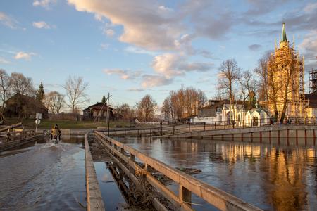 Kholuy, Ivanovo region, Russia - April 27, 2018: Flooded bridge in the village of Kholui, Yuzhsky district, Ivanovo region during the spring flood of the Teza River