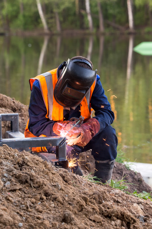 Balashikha, Moscow area, Russia - May 8, 2018: The worker conducts welding of metal designs at construction of the embankment on the river bank of Pekhorka