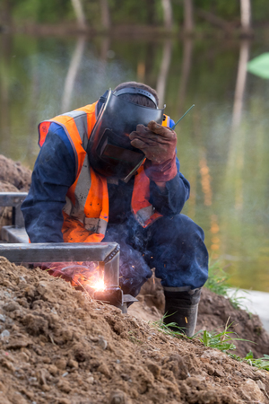 The worker conducts welding of metal designs at construction of the embankment on the river bank of Pekhorka