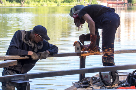 Balashikha, Moscow area, Russia - June 16, 2018: The worker cuts off parts of metal designs on construction of the embankment on the Pekhorka River in the city park