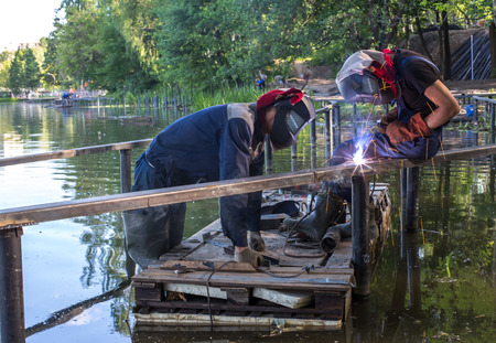 Balashikha, Moscow area, Russia - June 16, 2018: The worker welds metal designs on construction of the embankment on the Pekhorka River in the city park
