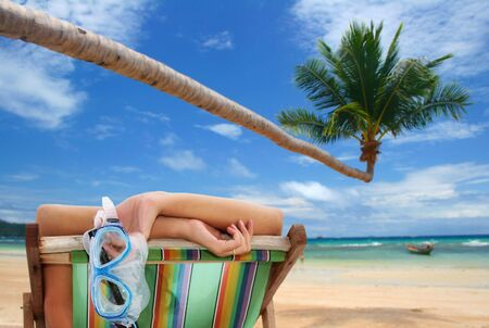 Woman in deckchair on tropical beach with coconut palm tree