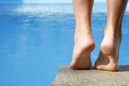 Woman about to dive into bright blue pool Stock Photo