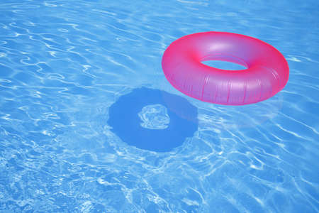 Pink inflatable ring in blue swimming pool