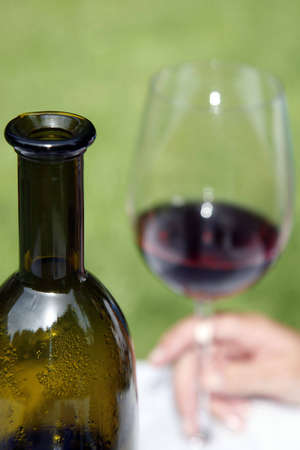 Red wine in glass with female hand and foreground bottle photo