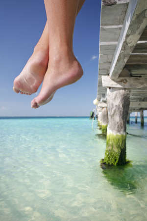 One of a large series. Great set of legs hanging over the edge of a tropical jetty. Stock Photo