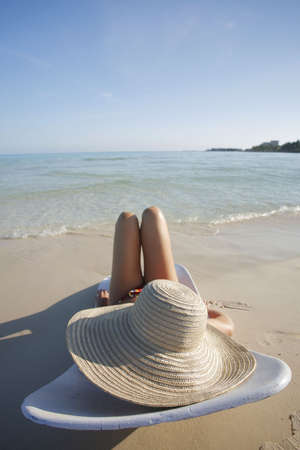 One of a large series. Pretty girl in big straw hat on a tropical beach.