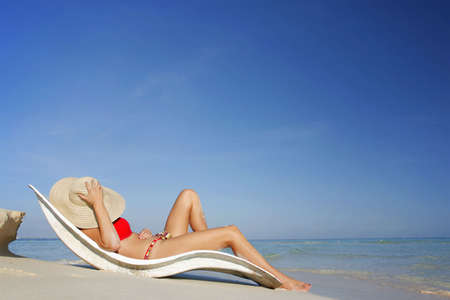 One of a long series of photos taken on the Mexican Caribbean coast. Woman sunbathing on luxury white recliner.