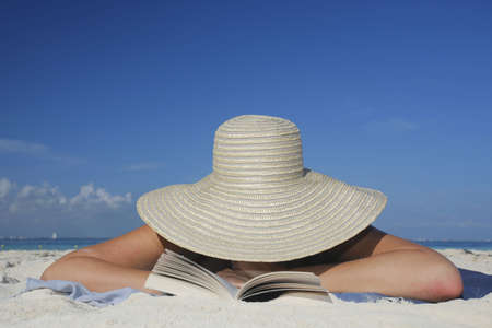 One of a long series of photos taken on the Mexican Caribbean coast. Woman reading on the beach with a big hat photo