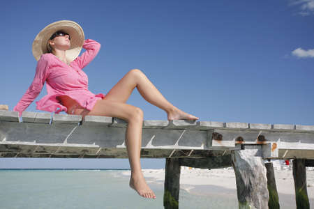One of a large series. Woman in pink kaftan sunbathing on a wooden jetty.