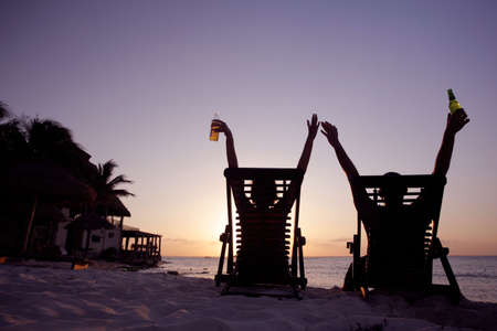 Couple stretching in deckchairs at sunset