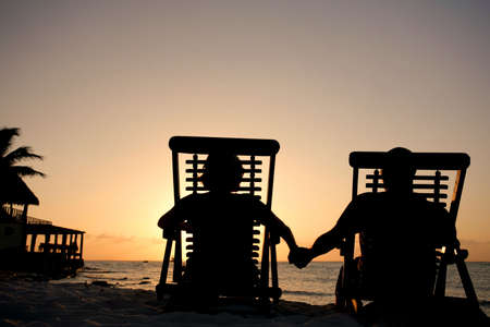 Couple in deckchairs holding hands at sunset Stock Photo - 2954028