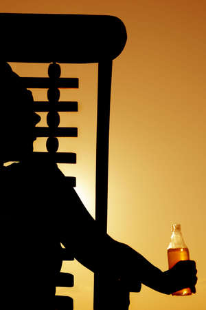 Woman drinking beer in a deckchair at sunset Stock Photo - 2954013