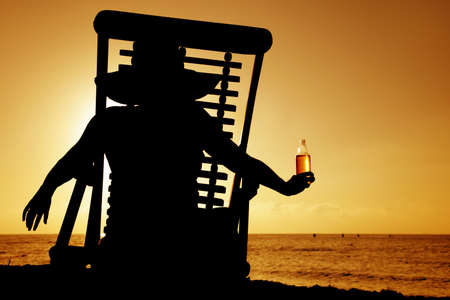 Woman drinking beer in a deckchair at sunset Stock Photo - 2954016