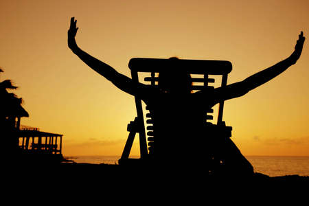 Woman stretching in a deckchair at sunset Stock Photo - 2954015