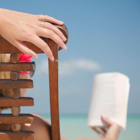 Woman reading in deckchair on tropical beach.