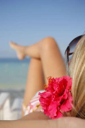 Woman sunbathing on a sun lounger on a tropical beach Stock Photo - 2954018