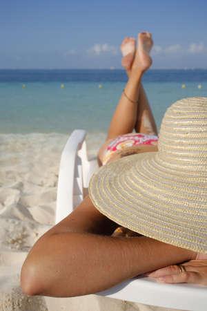 Woman sunbathing on a sun lounger on a tropical beach photo