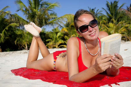 Pretty woman lying on the beach reading photo