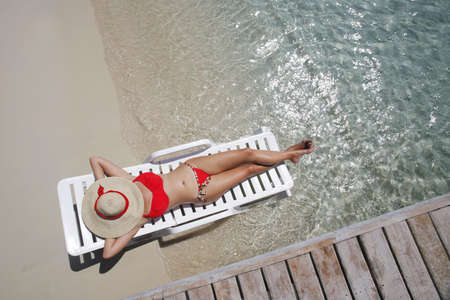 Pretty woman lying on the beach from an overhead perspective