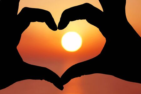 Womans hands making a heart shape in silhouette with the sunset behind