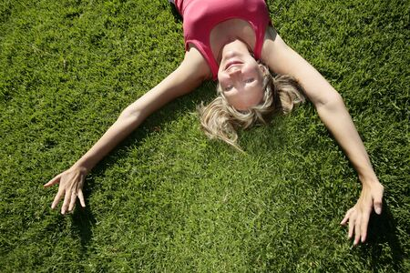 Woman lying on grass in the sunshine
