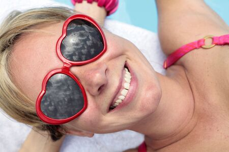 Woman in heart-shaped sunglasses besides a bright blue swimming pool