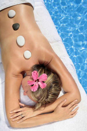 Woman at a spa with white stone on her forehead