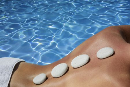 Woman with volcanic massage stones in front of a blue spa pool Stock Photo - 5093740