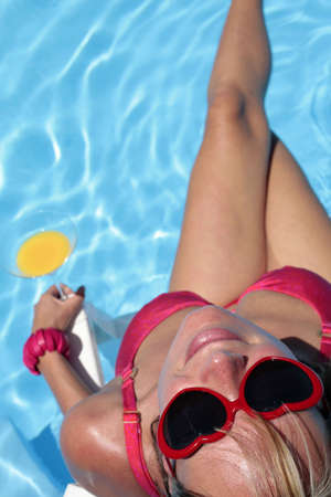 Woman in bikini and suglasses with cocktail and nice blue pool background