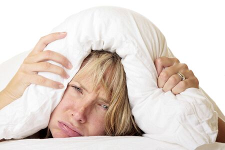 Woman ith her head under her pillow trying to sleep Stock Photo