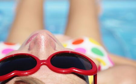 Close up of a pretty girl in sunglasses sunbathing by a blue pool Stock Photo - 5363981