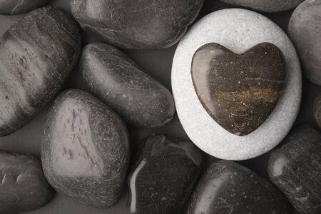 Heart shaped pebble framed on a dark pebble background Stock Photo