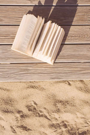 Open book on a boardwalk at sunset