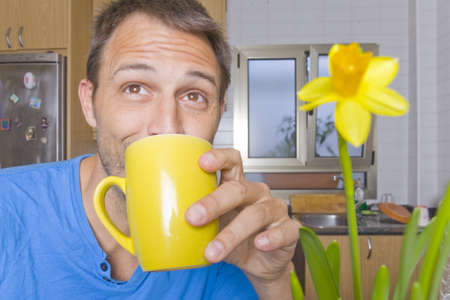 Man in his kitchen drinking coffee from a yellow mug. Stock Photo - 9297969