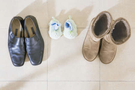 Three pairs of shoes by the front door of a home.  photo
