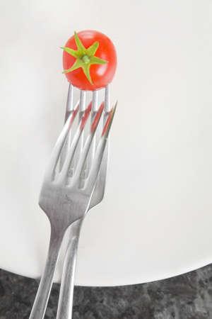 interlinked: Dos horquillas interrelacionados en un plato blanco con un peque�o tomate cherry