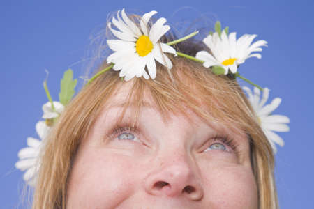 Smiling woman with a daisy chain around her head. Stock Photo - 9279674