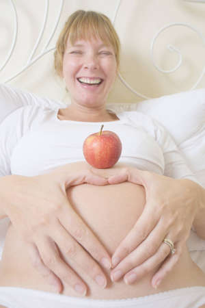 Smiling pregnant woman in high key with a red apple on her belly Stock Photo - 9277425