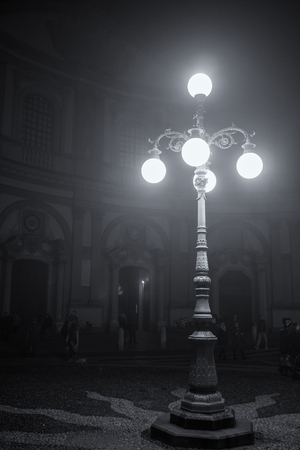 existed: Outdoor night time view of old street lamp in front of a cathedral in Italy during winter time