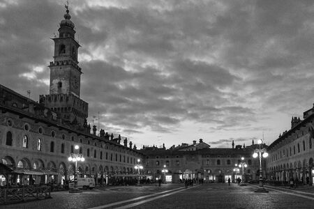 existed: Beautiful clouds in sky above the town square tower surrounded by old street lamps in Italy during the winter Stock Photo